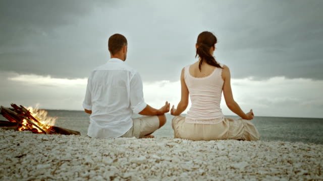 pan couple doing yoga on the beach - cross legged stock videos & royalty-free footage