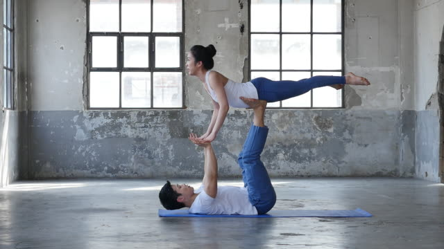 a couple doing yoga pose indoors - ärmelloses oberteil stock-videos und b-roll-filmmaterial