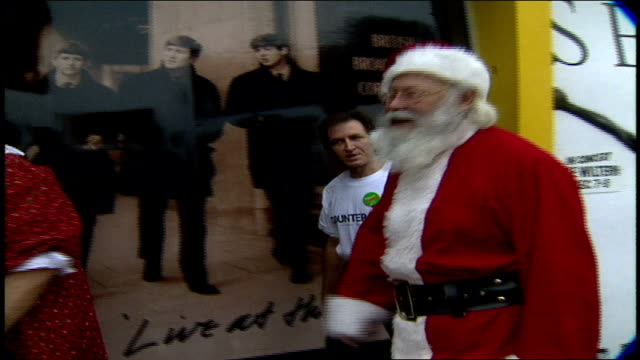 couple dressed as santa and mrs clause giving camera a lollipop and walking into tower records in los angeles california - weihnachtsfrau stock-videos und b-roll-filmmaterial