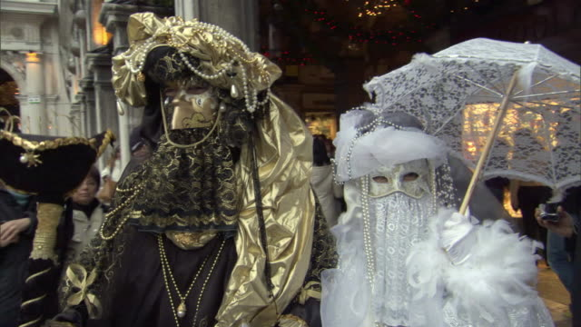 ms pan couple dressed in lavish carnival costumes walk in st mark's square in venice / venice, veneto, italy - fasching stock-videos und b-roll-filmmaterial