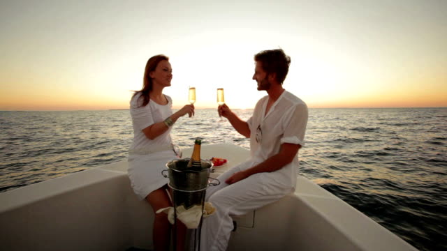 couple drinking champagne on boat at sunset - segeljacht stock-videos und b-roll-filmmaterial