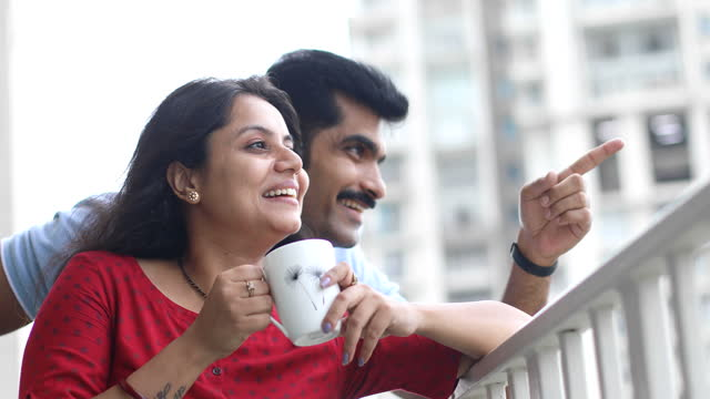 couple drinking coffee and admiring view from balcony - indian couple tea stock videos & royalty-free footage