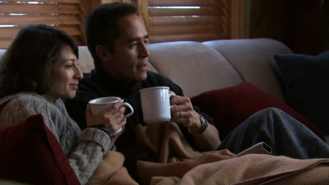 A couple drinking coffee on a couch
