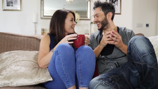 4K: Couple drinking coffee or tea on the sofa