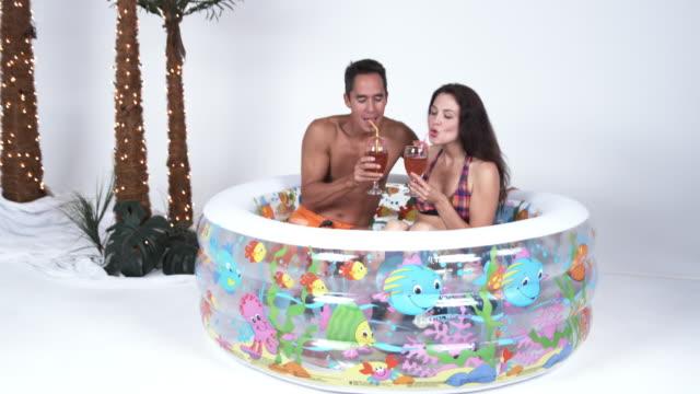 vidéos et rushes de ms pan couple drinking in wading pool / orem, utah, usa - pataugeoire