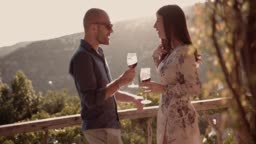 Couple drinking red wine on mediterranean rustic countryside house balcony