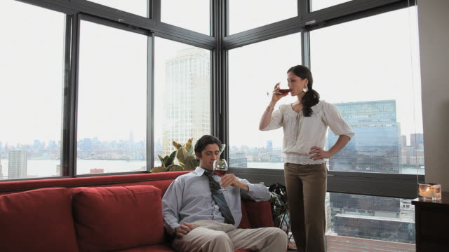 vídeos y material grabado en eventos de stock de ms couple drinking red wine sitting and embracing on sofa, , jersey city, new jersey, usa - vino tinto