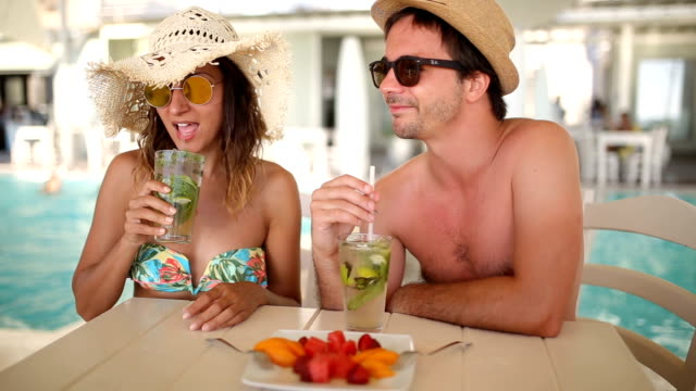 Couple drinking Summer cocktails by the pool