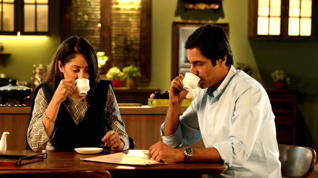 ms pan couple drinking tea while reading newspaper at home / delhi, india - indian couple tea stock videos & royalty-free footage