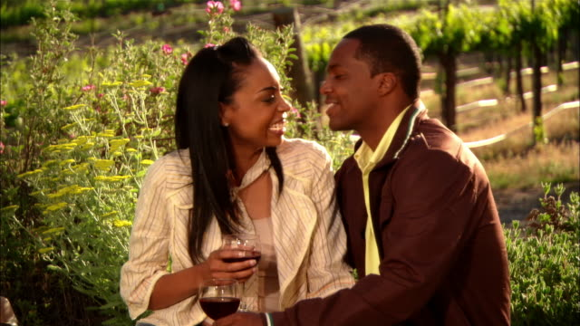MS Couple drinking wine and kissing in vineyard / Paso Robles, California, USA