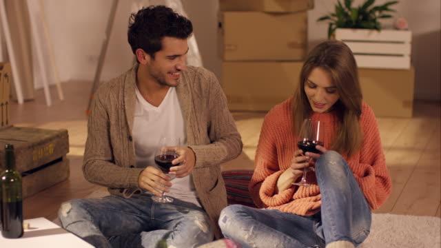 Paar, trinken Wein und sitzt auf Teppich