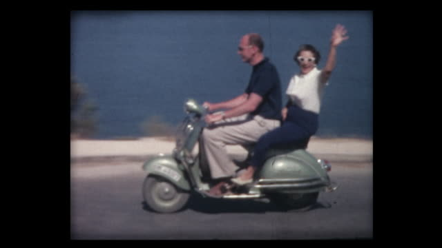 1963 couple drives by on vespa scooter - motorino video stock e b–roll