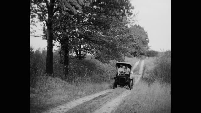 couple driving 1910's vintage car on country road - シボレー点の映像素材/bロール