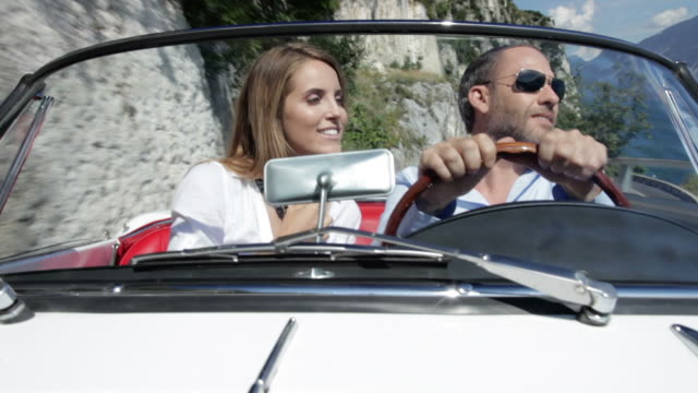 couple driving cabriolet - collector's car stock videos and b-roll footage