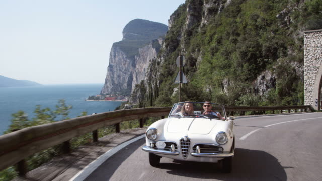 stockvideo's en b-roll-footage met couple driving cabriolet - overvloed