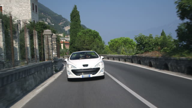 coppia guida in cabriolet - auto convertibile video stock e b–roll