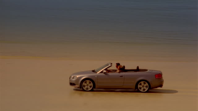 Couple driving convertible car across beach