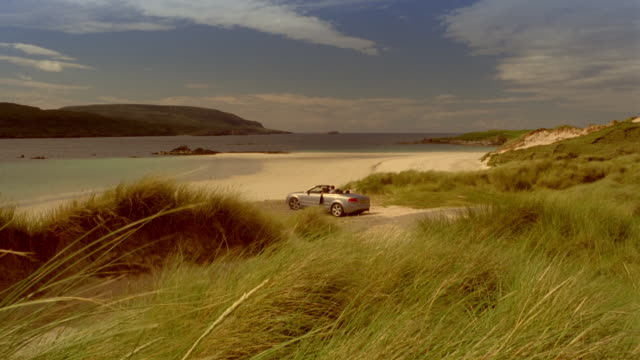 couple driving convertible car down beach / parking and getting out of car / hugging and looking at water / holding hands and running down beach / scotland - 高級車点の映像素材/bロール