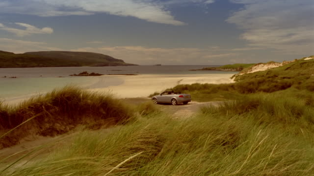 Couple driving convertible car down beach / parking and getting out of car / hugging and looking at water / holding hands and running down beach / Scotland
