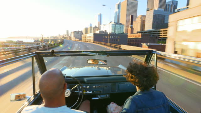 MS Couple driving convertible off road vehicle on city overpass on summer evening