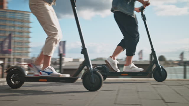 vídeos de stock e filmes b-roll de couple driving electric kick scooters in city - vida urbana