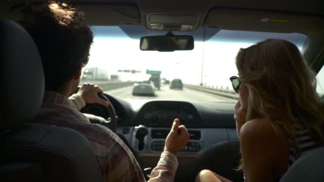 ms pov couple driving in car on highway, woman talking on mobile phone / belt parkway, new york state, usa - vehicle interior stock videos & royalty-free footage