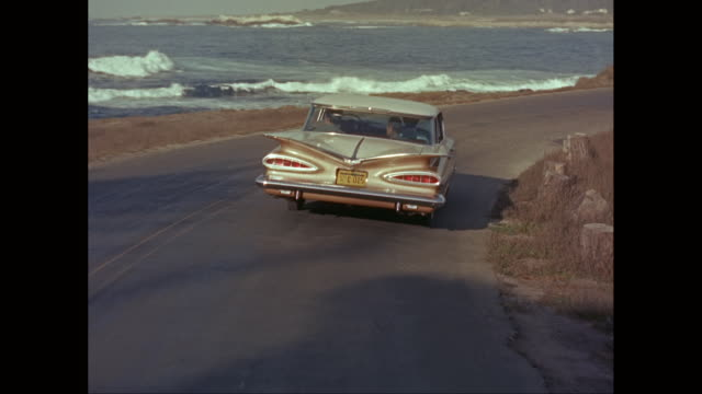 ws pov couple driving in car on road next to ocean / united states - on the move video stock e b–roll