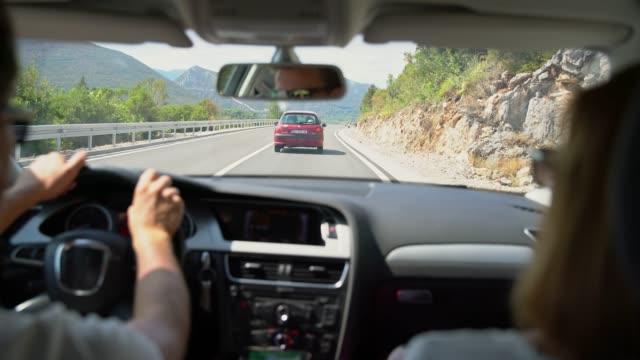 vidéos et rushes de couple ms au volant de voiture sur la route ensoleillée, profitant de voyage sur la route - deux personnes