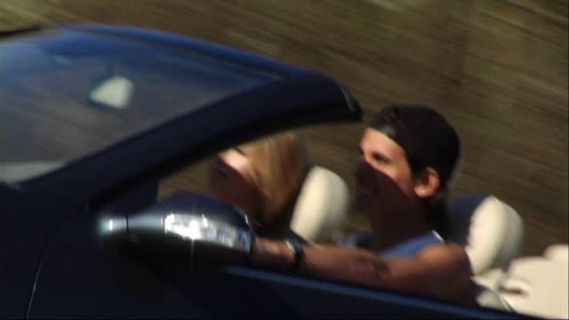 couple driving in convertible car - berretto da baseball video stock e b–roll
