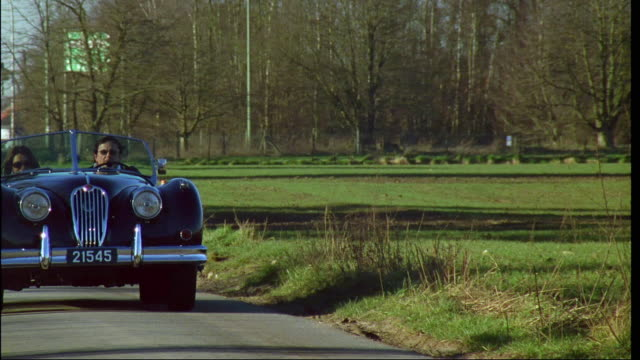 ms, couple driving in convertible vintage car on rural road, brussels, belgium - collector's car stock videos and b-roll footage
