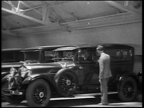 b/w 1928 couple driving off in new lincoln car as salesman looks on / newsreel - venditore video stock e b–roll
