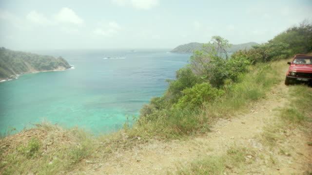 ws pov couple driving off-road vehicle by ocean / scarborough, tobago, trinidad and tobago  - trinidad trinidad and tobago stock videos & royalty-free footage