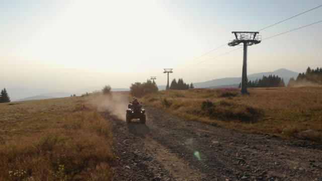 couple driving quad on mountain - quadbike stock videos & royalty-free footage