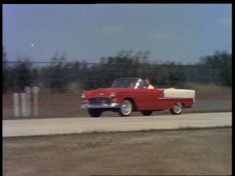 stockvideo's en b-roll-footage met 1955 pan couple driving red + white convertible chevrolet bel air on country highway - 1955