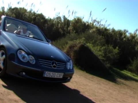 couple driving to beach in convertible car - 野球帽点の映像素材/bロール