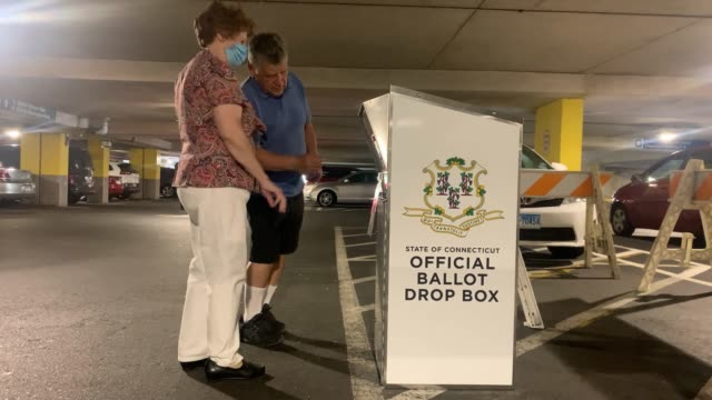 a couple drops off her connecticut 2020 presidential primary ballots at a secure ballot drop box on august 11 2020 in stamford connecticut due to the... - voting ballot stock videos & royalty-free footage