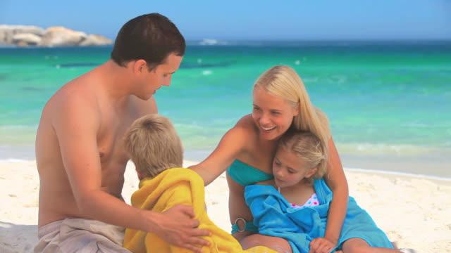 couple drying their children on a beach / cape town, western cape, south africa - タオルにくるまる点の映像素材/bロール