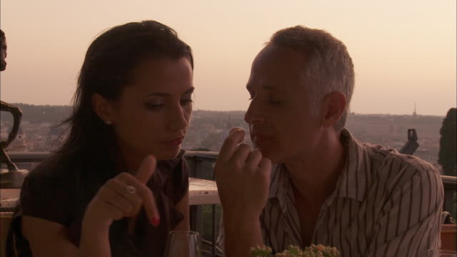 CU Couple eating and kissing at terrace restaurant, Rome, Italy