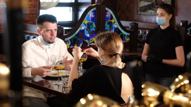 paar essen in bar wieder öffnen nach quarantäne-beschränkung - entfernt stock-videos und b-roll-filmmaterial