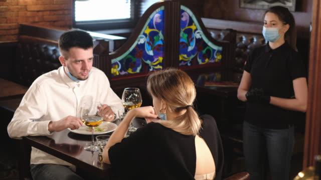 vídeos de stock e filmes b-roll de couple eating at bar reopening after quarantine restriction - doença infeciosa