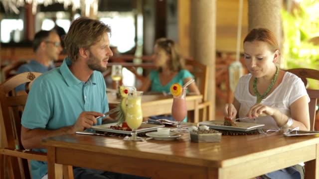 vídeos y material grabado en eventos de stock de couple eating at tropical restaurant - cóctel tropical