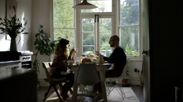 couple eating breakfast in sunny kitchen - table stock videos & royalty-free footage