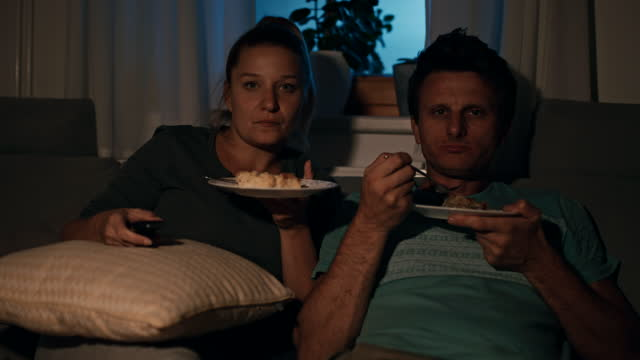 ms couple eating desserts in front of the tv at night - 1 minute or greater stock videos & royalty-free footage