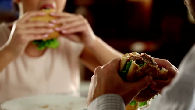couple eating fast food in a restaurant - hamburger stock videos and b-roll footage