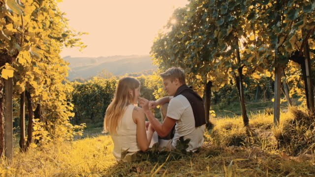 Couple eating grapes in the vineyard
