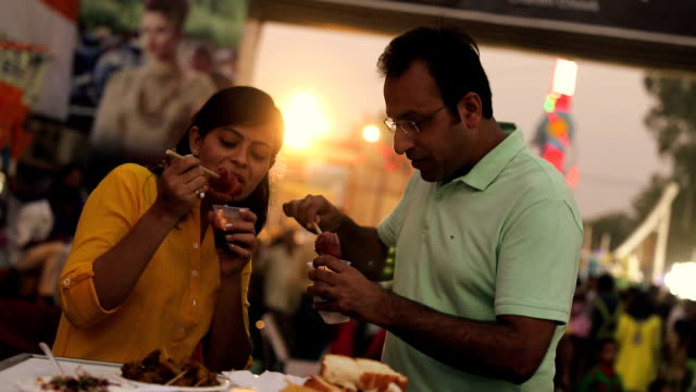 Couple eating ice candy at fair, Delhi, India
