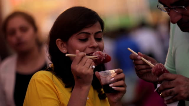 stockvideo's en b-roll-footage met couple eating ice candy in the market, delhi, india - markt