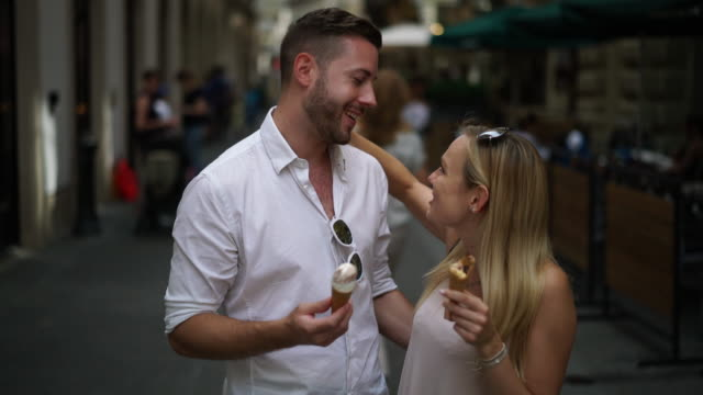 couple eating ice cones in city
