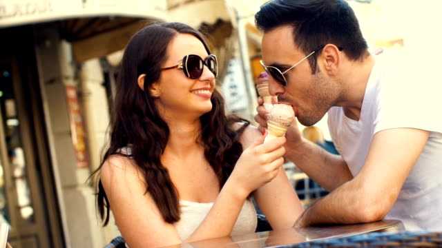 couple eating ice cream at a cafe. - toned image stock videos & royalty-free footage