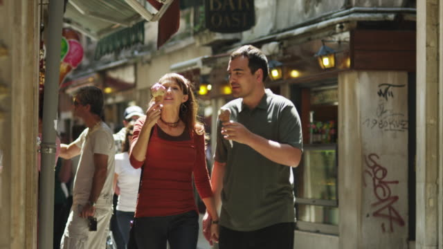 ms couple eating ice cream walking down old town street / venice,veneto - gelato stock videos and b-roll footage